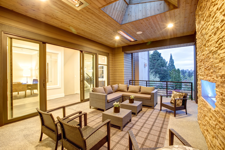 Dreamy outdoor covered patio with stone fireplace, a beadboard ceiling with skylight, rattan armchairs, sofa and ottomans overlooking the expansive backyard. Northwest,USA Stock Photo