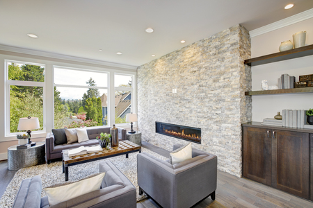 Modern great room features a floor to ceiling stone fireplace, gray tufted sofa paired with two gray armchairs over fluffy rug. Northwest, USA