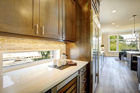 贅沢な台所は茶色の木の前部上部のキャビネットを特色にし、小さい窓の下の白い水晶カウンタートップとペアになっているガラスドアのワインク