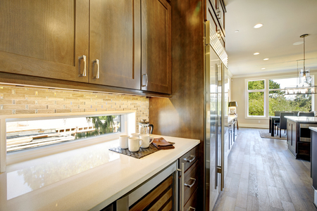 Luxury kitchen features brown wood front upper cabinets and shaker lower cabinets fitted with a glass door wine cooler paired with a white quartz countertop under a small window. Northwest, USA Stockfoto