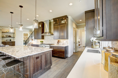 Luxury kitchen accented with large granite kitchen island, taupe tile backsplash, natural brown wood cabinets and lots of natural light. Northwest, USA