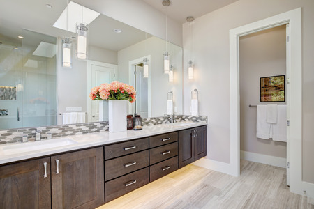 Contemporary master bathroom features a dark dual vanity cabinet featuring his and her sinks framed by a white countertop with mosaic backsplash under  a large full mirror. Northwest, USA