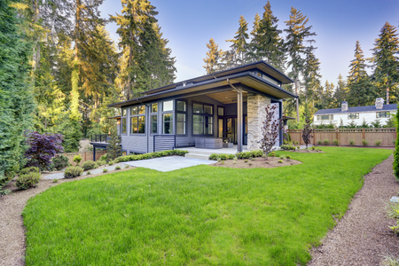 New modern home features a backyard with luxurious covered patio and green grass. Northwest, USA