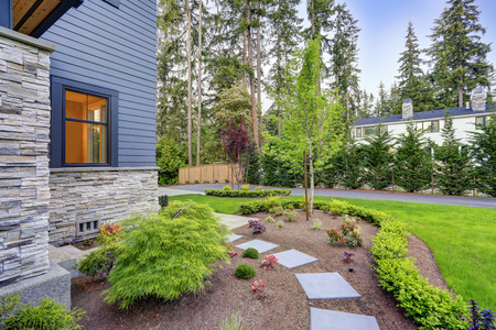 Exterior of grey two-story mixed siding home. View of a gravel path leading to the backyard and green grass in the garden. Northwest, USA