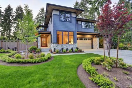 Luxueus nieuw huis met opstanden. Trendy grijze twee verdiepingen gemengde gevelbeplating buitenkant in Bellevue met goed onderhouden voortuin. Northwest, VS.
