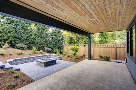 New modern home features a backyard with covered patio accented with a wood plank ceiling and a rectangular fire pit, made of concrete and slate tiles. Northwest, USA