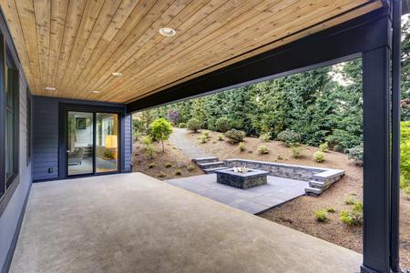 Nova casa moderna possui um quintal com pátio coberto acentuado com um teto de tábua de madeira e uma fogueira retangular, feita de concreto e telhas de ardósia. Noroeste, EUA