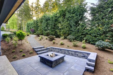 Das neue moderne Haus verfügt über einen Hinterhof mit einer rechteckigen Feuerstelle aus Beton, die von Schieferpflastern eingerahmt wird, und blickt auf den üppigen Garten. Nordwesten, USA