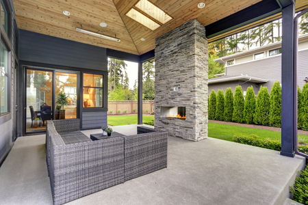 New modern home features a backyard with covered patio accented with stone fireplace, vaulted ceiling with skylights and furnished with gray wicker sofa placed on concrete floor. Northwest, USA Stock Photo