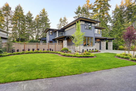 Luxurious home design with modern curb appeal in Bellevue features gray wood siding, stone columns and two garage spaces. Northwest, USA Stock Photo