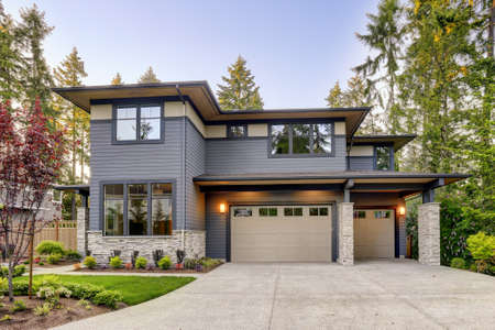 New construction home exterior with contemporary house plan features gray wood siding, stone columns and two garage spaces. Northwest, USA
