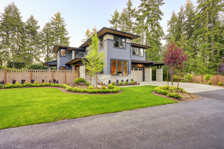 Luxurious new home with curb appeal. Trendy grey two-story mixed siding exterior in Bellevue with well manicured front yard and asphalt driveway. Northwest, USA