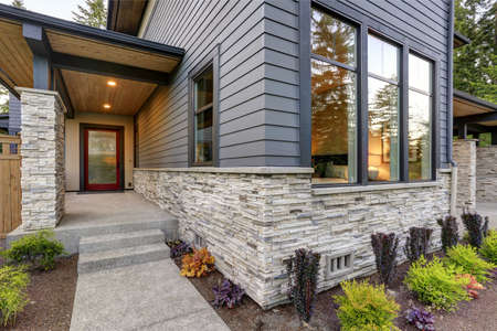 Luxurious new home with curb appeal. Trendy grey two-story exterior in Bellevue with large picture windows, stone siding, covered porch and concrete pathway. Northwest, USA