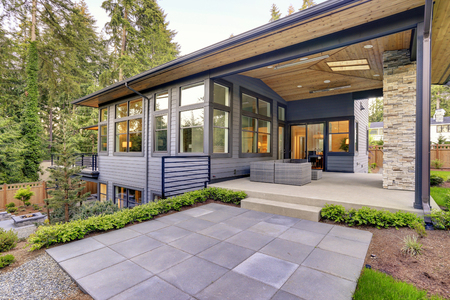New modern home features a backyard with covered patio accented with stone fireplace, vaulted ceiling with skylights and furnished with gray wicker sofa placed on concrete floor. Northwest, USA Stockfoto