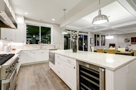 Gourmet-Küche verfügt über weiße Shaker-Schränke mit Marmor-Arbeitsplatten, Stein U-Bahn Fliesen Backsplash und wunderschöne Küche Insel. Nordwest, USA Standard-Bild