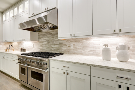 Gourmet-Küche verfügt über weiße Shaker-Schränke mit Marmor-Arbeitsplatten gepaart mit Stein U-Bahn Fliesen Backsplash und Edelstahl-Kapuze über acht Brenner Gas-Bereich. Nordwest, USA Standard-Bild - 89679773