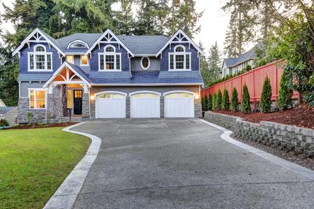 Exterior luxuoso em casa com revestimento de vinil azul e acabamento branco. A calçada de concreto longo leva a três espaços de garagem anexados. Belo atrativo. Noroeste, EUA