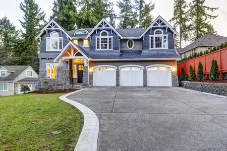 Luxurious home exterior with blue vinyl siding and white trim. Long concrete driveway lead to three attached garage spaces. Beautiful curb appeal. Northwest, USA Stock Photo - 89286560