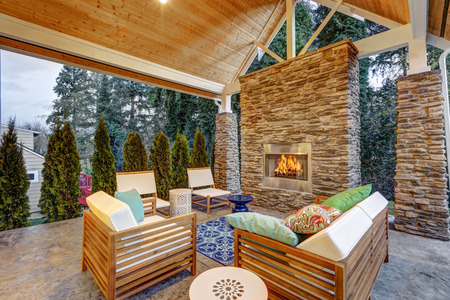 Chic covered back patio with built in gas fireplace, stone pillars, plank vaulted ceiling over cozy teak wood sofa set topped with white cushions and green pillows. Northwest, USA  Stock Photo