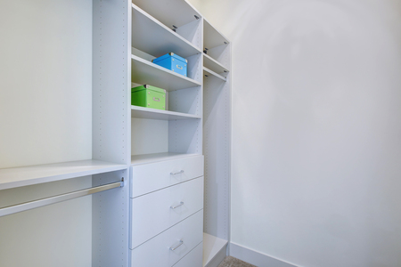 Empty walk-in closet with open shelves and grey carpet floor. Northwest, USA