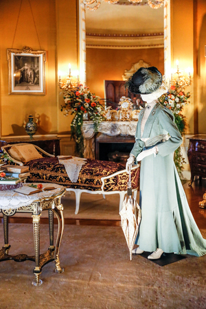 ASHEVILLE, NORTH CAROLINA - MARCH 4, 2017: Biltmores costume exhibition. The House of Mirth is featured in Edith Vanderbilts bedroom, with gilded portrait frames and mirrors. Editorial
