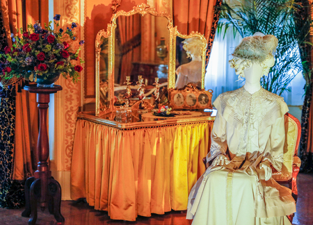 ASHEVILLE, NORTH CAROLINA - MARCH 4, 2017: Biltmores costume exhibition. The House of Mirth is featured in Mrs Vanderbilts bedroom. Costumes were arranged with mirrors to see the backs of both.