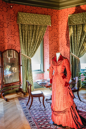 appointed: ASHEVILLE, NORTH CAROLINA - MARCH 4, 2017: Biltmores costume exhibition. The rich red gown from Portrait of a Lady is right at the burgundy papered walls bedroom appointed with sumptuous draperies.