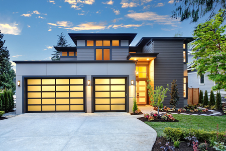 Piękna fasada współczesnego domu z dwoma miejscami garażowymi o zachodzie słońca. Northwest, USA