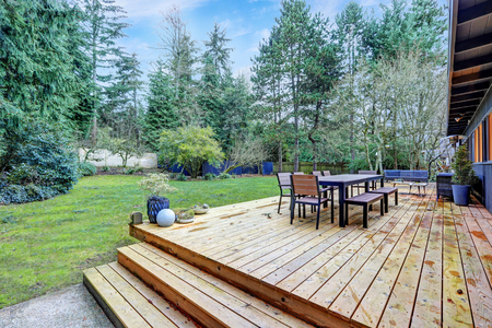 View of large back deck with outdoor furniture overlooking grass filled backyard. Northwest, USA Stock fotó