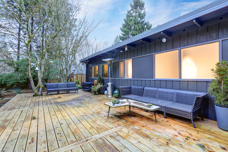 View of large back deck with outdoor furniture overlooking grass filled backyard. Northwest, USA Editorial