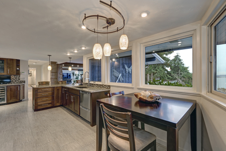 Beautiful modernized epicurean kitchen with breakfast nook features natural brown cabinets, granite countertops and mosaic backsplash. Northwest, USA