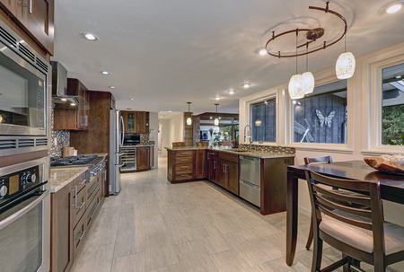 Beautiful modernized epicurean kitchen with natural brown cabinets, granite countertops and mosaic backsplash. Northwest, USA Stock Photo