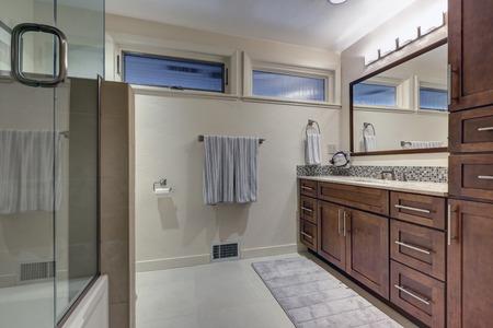 새로 개조 된 현대식 2 색 욕실에는 천연 갈색 세면대가 갖추어져 있으며 많은 수납 공간, 모자이크 백 스플래시 및 유리 샤워 시설이 갖추어져 있습니