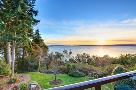 Modern two story panorama house exterior. Awesome sunset view of Puget Sound from the second floor deck. Northwest, USA