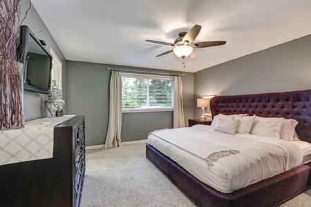 Master bedroom suite with gorgeous queen size upholstered bed accented with burgundy tufted headboard flanked by nightstands with glass lamps and facing large chest of drawers. Northwest, USA