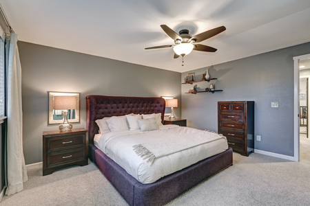 Master bedroom suite with gorgeous queen size upholstered bed accented with burgundy tufted headboard flanked by nightstands with glass lamps and a chest of drawers by gray wall. Northwest, USA