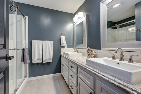 En-suite bathroom with nice design: dark grey walls framing long double sink white bathroom vanity topped with granite counter paired with white backsplash and a glass walk-in shower. Northwest, USA Stock Photo