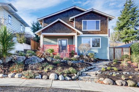 Nice Craftsman home exterior on blue sky background. Well kept frontyard with natural stone landscape design. Northwest, USA Stock Photo