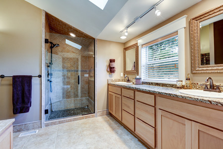 Master bathroom interior with large double sink vanity cabinet topped with granite countertop, glass walk-in shower and vaulted ceiling with skylight. Northwest, USA Stock Photo