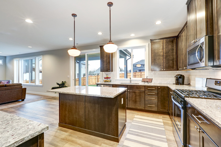 Light filled Northwest kitchen design with kitchen island, natural brown cabinets topped with granite countertops and paired with white backsplash. Northwest, USA Archivio Fotografico
