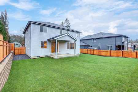 New luxury home with pale blue wood siding features covered back porch with concrete floor. Fully fenced spacious backyard boasts perfectly kept lawn. Northwest, USA