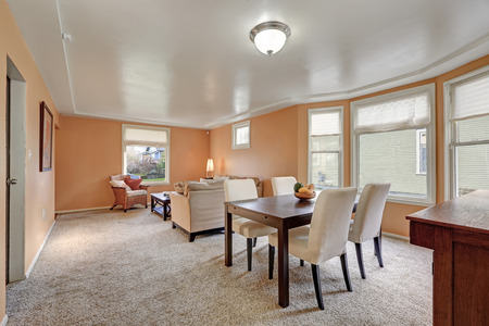 Cozy living and dining room interior with peach walls, dining area filled with dark stained dining table lined by beige upholstered chairs. Northwest, USA
