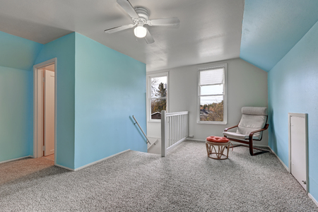 Second floor landing with blue walls, furnished with comfortable reading chair in the corner with wicker ottoman topped with red tufted cushion, grey wall to wall carpet floor. Northwest, USA