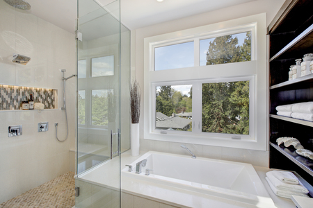Contemporary master bathroom features glass walk-in shower, drop-in tub with a perfect window view. Northwest, USA Stock Photo
