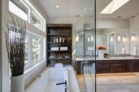현대식 마스터 욕실에는 어두운 이중 창고, 유리제 대형 샤워 실, 드롭 인 욕조 및 선반이있는 열린 캐비닛이 있습니다. 미국 노스 웨스트 스톡 콘텐츠