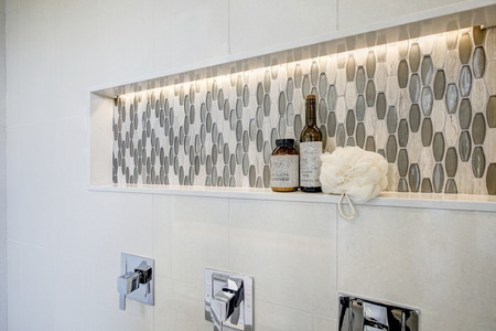 Stunning walk-in shower features white tile surround, shower niche  fitted with mosaic gray tiles. Northwest, USA   写真素材