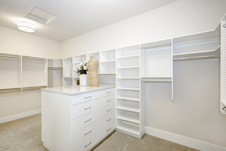 Huge white walk-in closet with shelves, drawers and clothes rails. Northwest, USA
