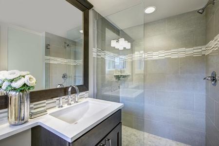 モダンなバスルームは、大型完全ミラーとガラス ウォークイン シャワーの下の長方形のシンク装備暗い虚栄心のキャビネットを備えています。米国