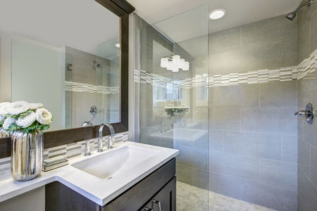 Das moderne Badezimmer verfügt über einen dunklen Waschtisch mit einem rechteckigen Waschbecken unter einem großen Spiegel und einer ebenerdigen Glasdusche. Nordwesten, USA Standard-Bild - 89931569