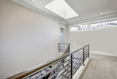 Second floor landing in light gray tones features skylight over the staircase with metal horizontal hand rails. Northwest, USA